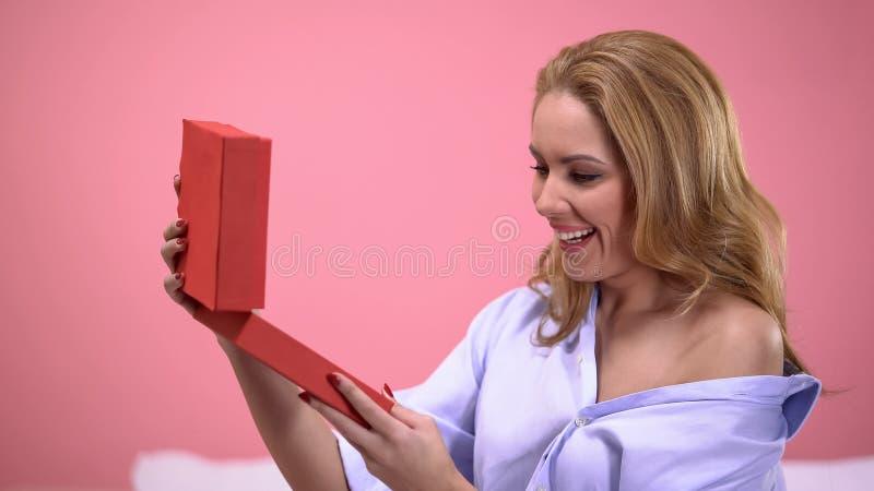 Förförisk kvinna som är jätteglad med dyrbar gåva i röd gåvaask, valentindag arkivfoton