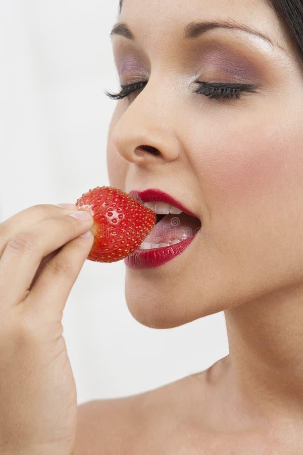 Förförisk kvinna som äter jordgubben arkivbild