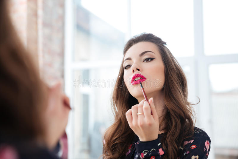 Förförisk kvinna som applicerar röd läppstift till kanter som ser i spegel arkivfoton
