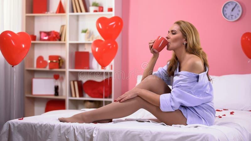 Förförisk kvinna som dricker varmt kaffe i säng, rum som dekoreras med hjärtaballonger fotografering för bildbyråer