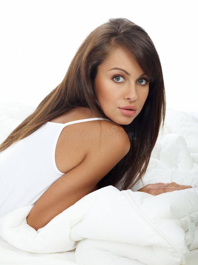 Förförisk kvinnabenägenhet för långt hår på vit säng royaltyfri foto