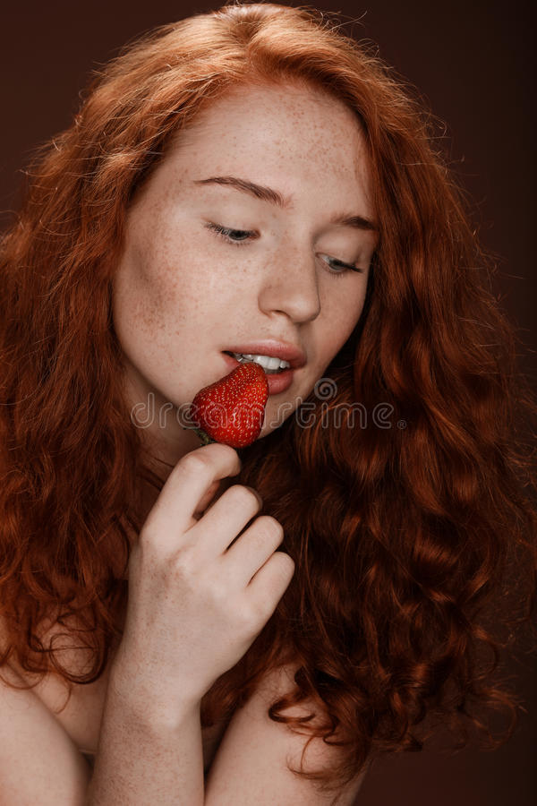 Förförisk rödhårig mankvinna som äter den röda jordgubben, på brunt royaltyfri fotografi