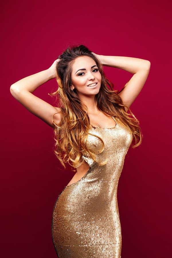 Förförisk ung flicka i guld- klänning royaltyfria bilder