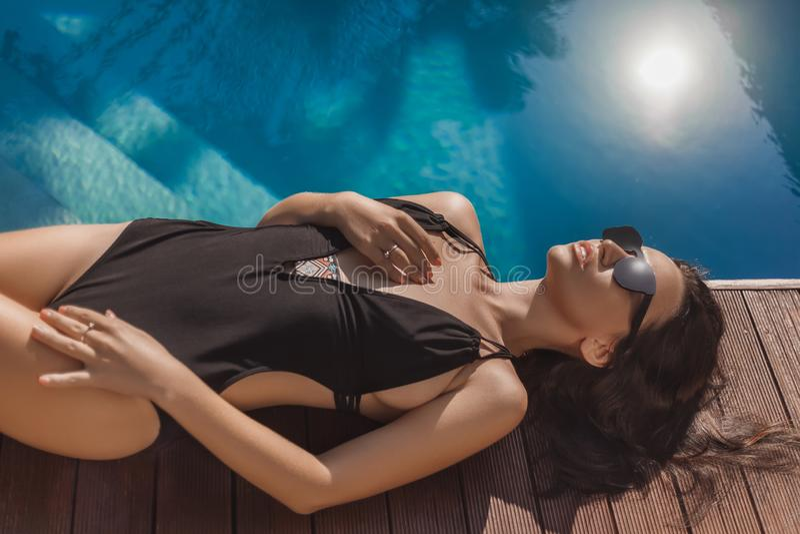 förförisk ung kvinna i svart ligga för baddräkt arkivfoton