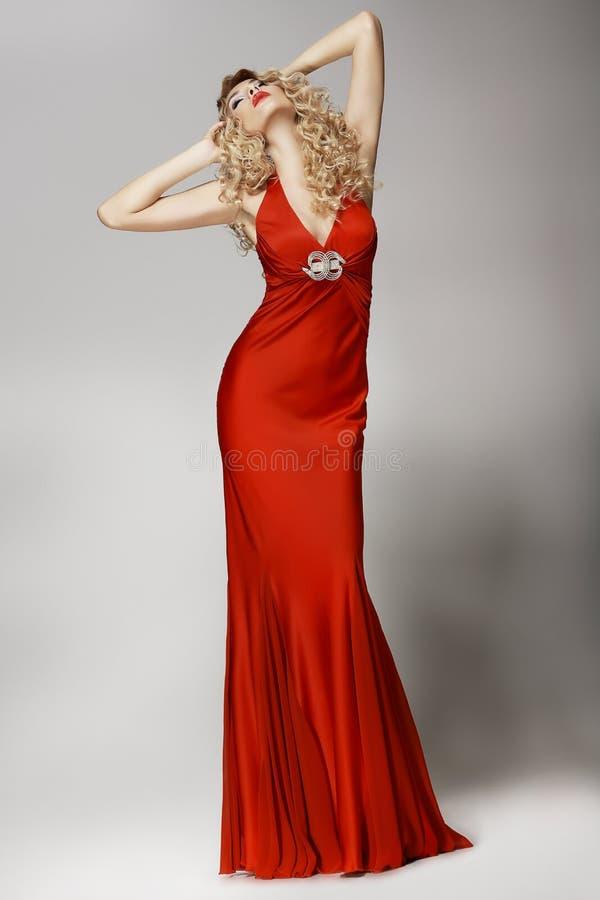 Förförisk välformad kvinna i rött posera för klänning royaltyfri fotografi