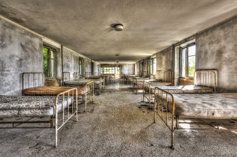 Förfallen sovsal i en övergiven barnsjukhus royaltyfria foton