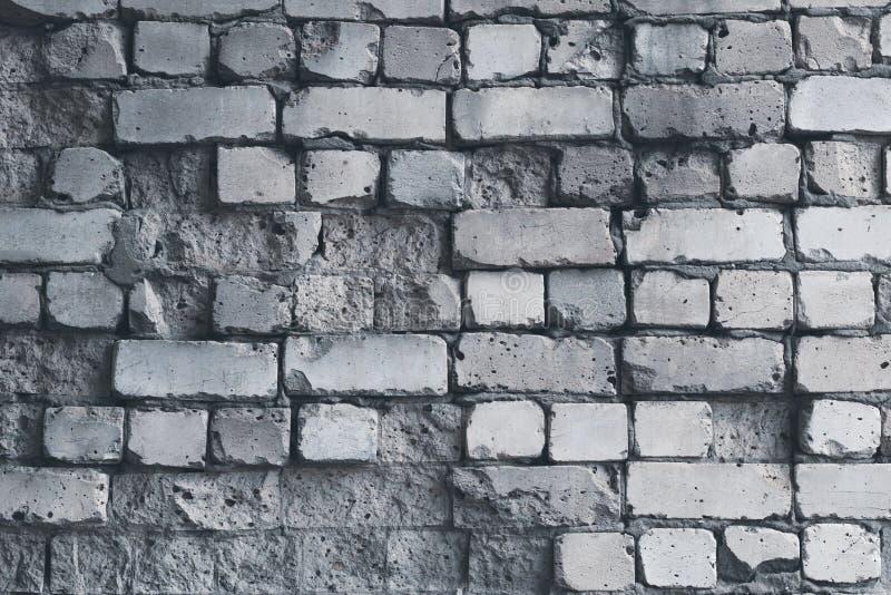 Förfallen vit tegelstenvägg, grungebakgrund Grå modell för tegelstenvägg, riden ut textur Grå färgstenbetongvägg Gammalt sprucket royaltyfri fotografi