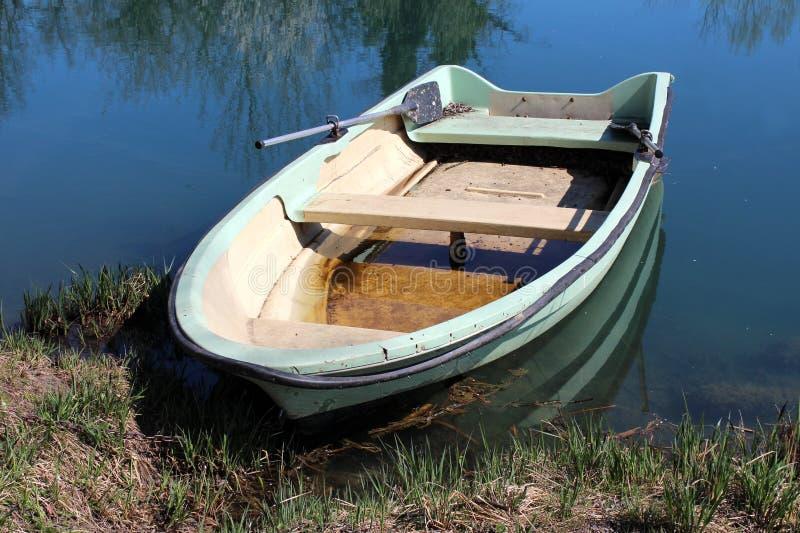 Förfallet gammalt ljust - grönt glasfiberflodfartyg som binds till flodbanken som omges med oklippt gräs och den klara blåa flode fotografering för bildbyråer