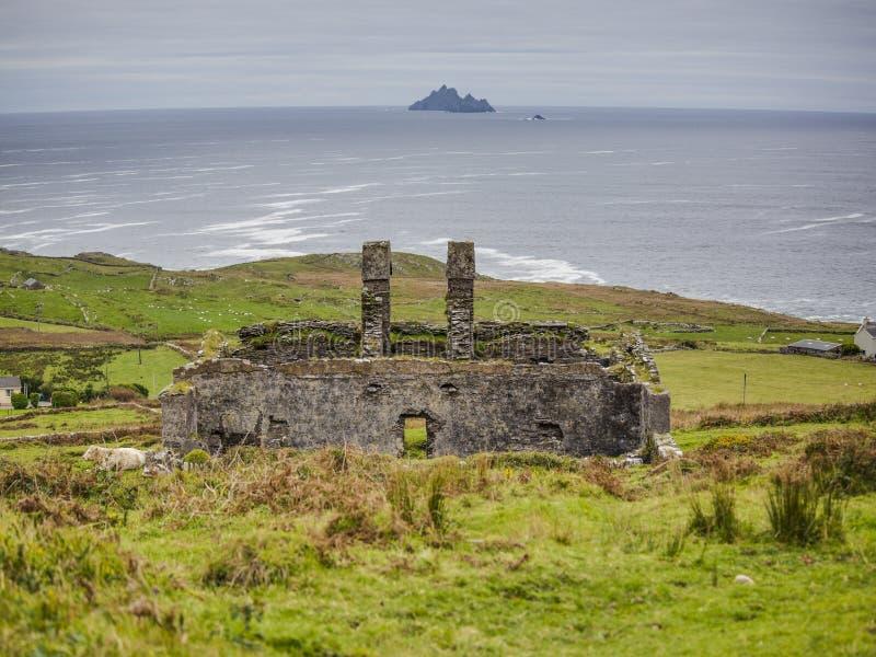 Förfallet stena byggnad i irländsk bygdregion med Skelig Michael Island arkivbilder