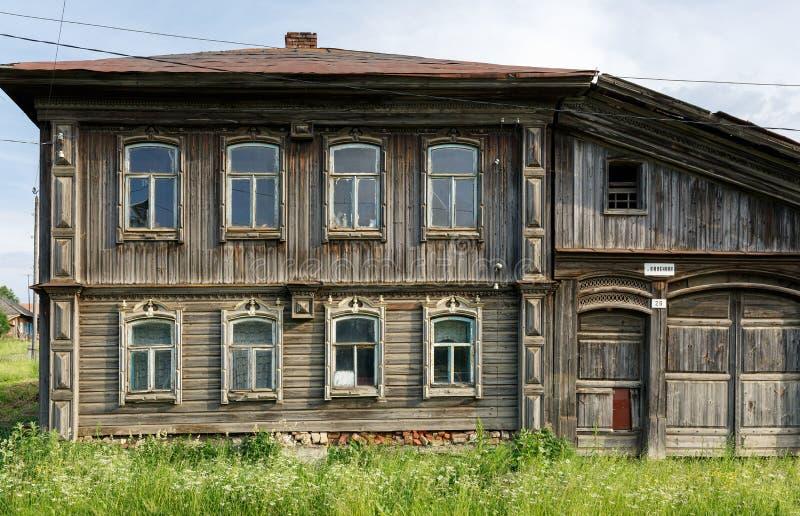 Förfallet träbostads- hus med den sned fasaden By av Visim, Ryssland royaltyfri foto