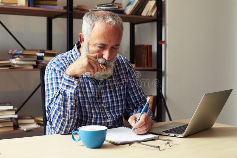 Författare som äter kakor och arbete i hans rum royaltyfri bild