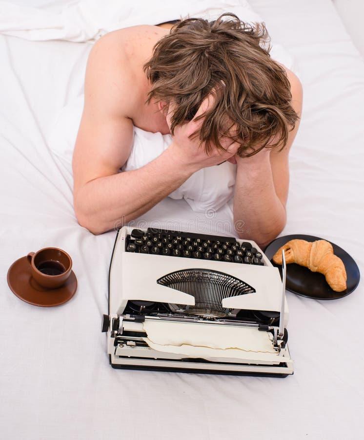 Författaredrinkkaffe har frukosten i säng Brist av inspiration eller idén Kreativitetkris Manförfattaren lägger sängsängkläder royaltyfria bilder