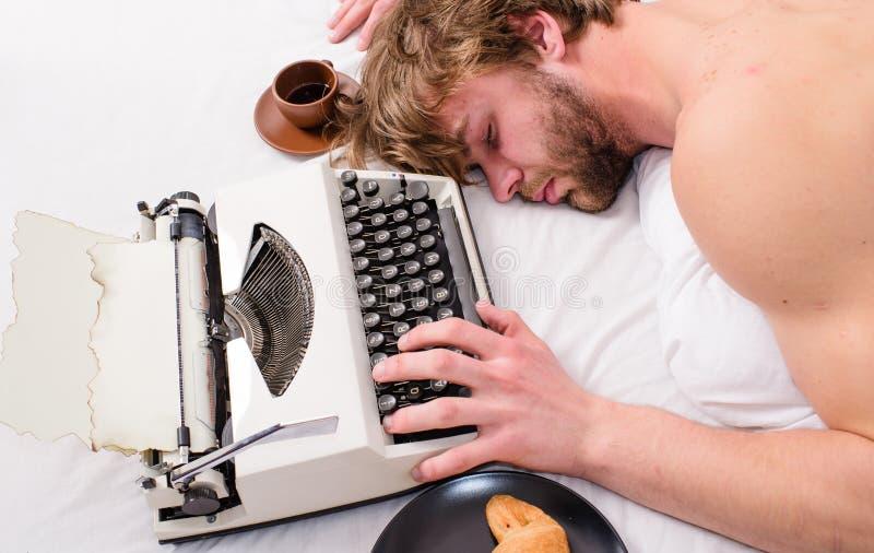 Författaren rufsade till hår faller sovande, medan skriv boken Arbetsnarkomanen faller sovande Man med skrivmaskinssömn evakuera arkivbilder