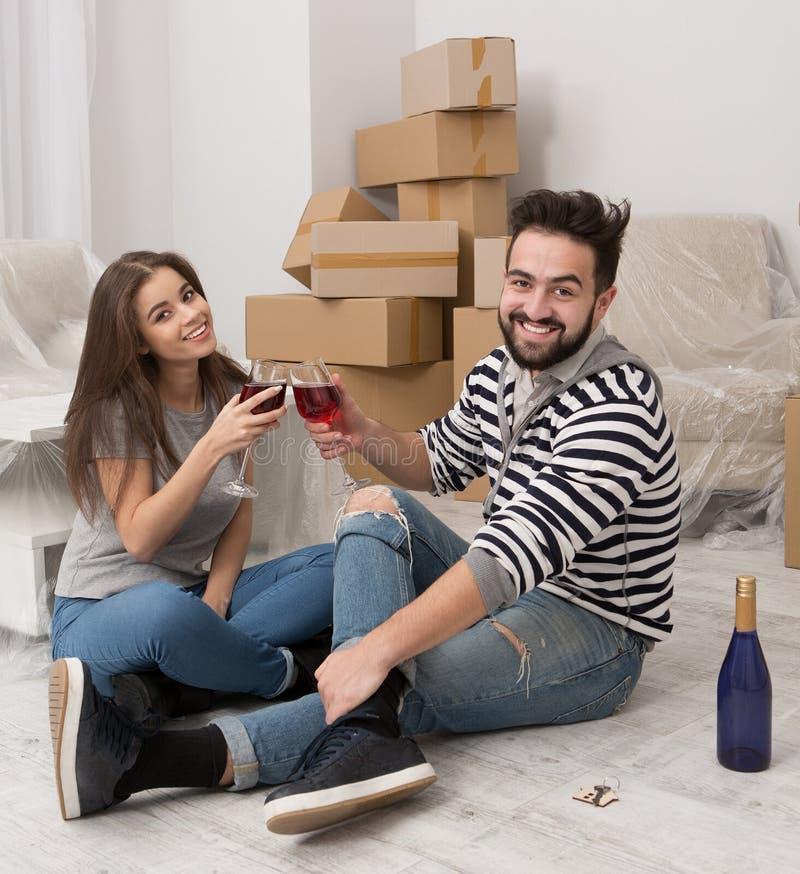Förflyttning är dags för glädje och lycka Par som firar förflyttning till det nya hemmet arkivbild