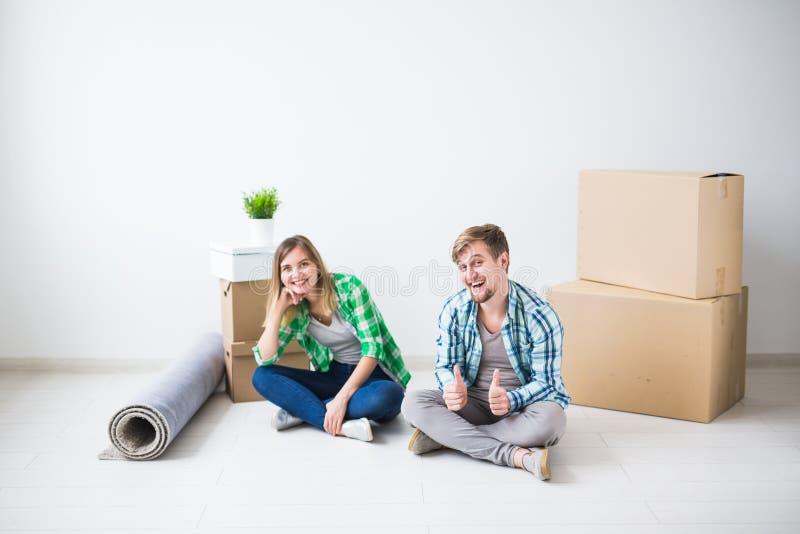 Förflyttning, fastighet och rörande begrepp - det unga parfolket flyttade sig till en ny lägenhet royaltyfria foton