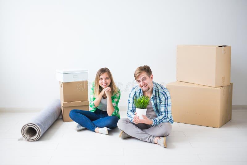 Förflyttning, fastighet och rörande begrepp - ungt gladlynt par som flyttar sig in i deras nya hem royaltyfria bilder