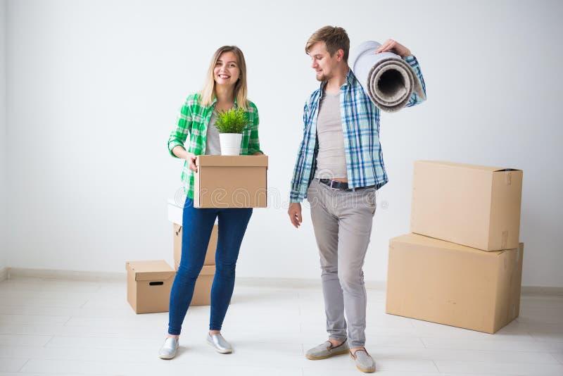 Förflyttning, fastighet och rörande begrepp - ungt gladlynt par som flyttar sig in i deras nya hem arkivbild