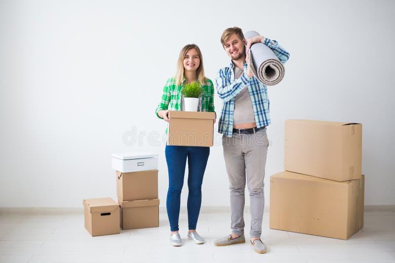 Förflyttning, nytt hem och fastighetbegrepp - ungt par som upacking i deras nya lägenhet tillsammans royaltyfria foton