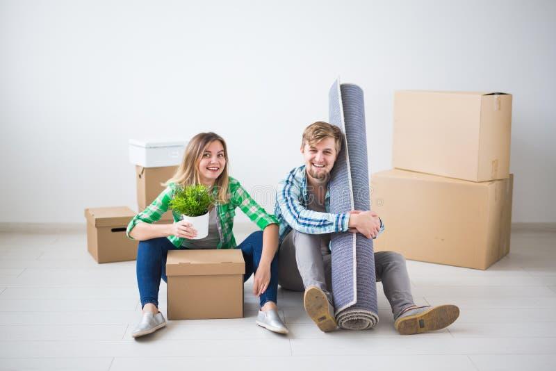Förflyttning, nytt hem och fastighetbegrepp - ungt par som upacking i deras nya lägenhet tillsammans fotografering för bildbyråer