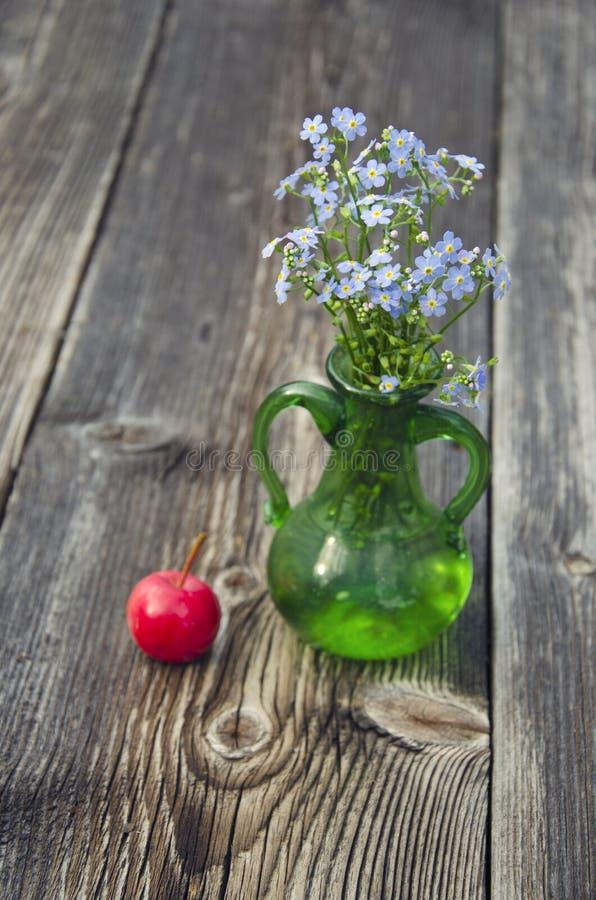 Förgätmigejen blommar i vas och äpple på träbakgrund arkivfoto