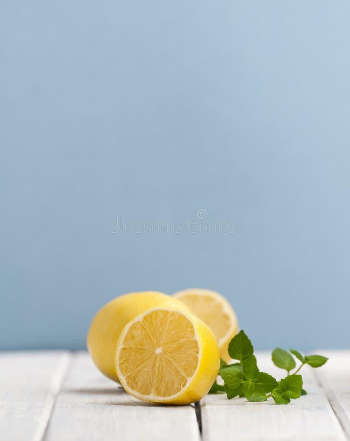 Förgrena sig halvan en mogen citron och en mintkaramell på en vit trätabell på a arkivfoton