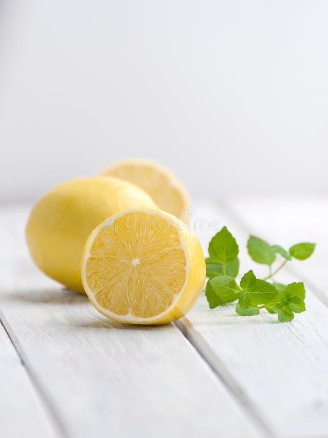 Förgrena sig halvan en mogen citron och en mintkaramell på en vit trätabell royaltyfria foton