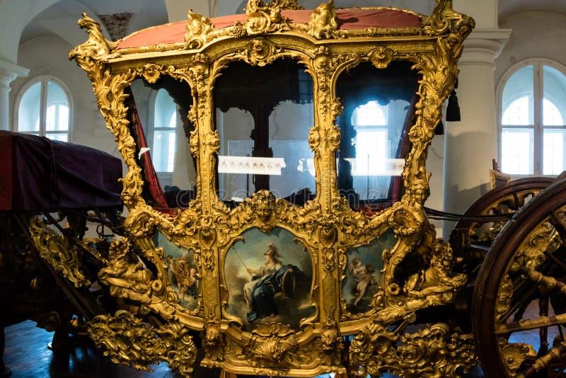 Förgylld utsmyckad historisk vagn i ett museum royaltyfri fotografi