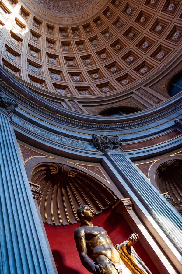 Förgyllt bronsstaty av det Hercules anseendet i rund korridor under coffered takkupol Statyn av Hercules av teatern av arkivfoto