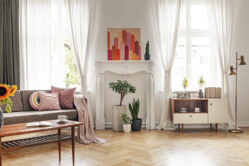 Förhängear på fönster och affischen i den vita vardagsruminre med soffan och skåpet Verkligt foto royaltyfria foton