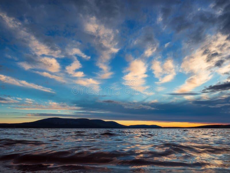 Förhäxa färgrik solnedgång över sjön royaltyfri fotografi