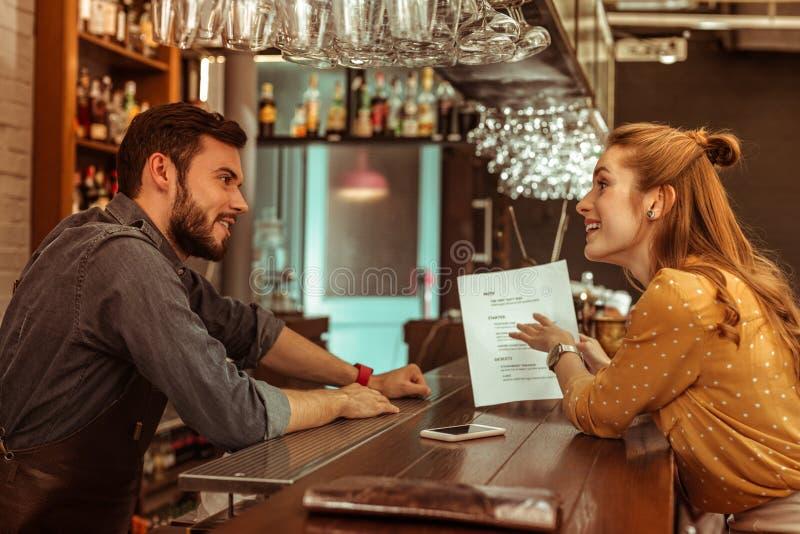 Förhäxa kvinnan som diskuterar en meny med den stiliga mörker-haired skäggiga bartendern royaltyfria bilder