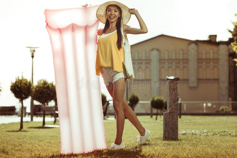 Förhäxa skönhetanseende med en rosa uppblåsbar luftmadrass utomhus fotografering för bildbyråer