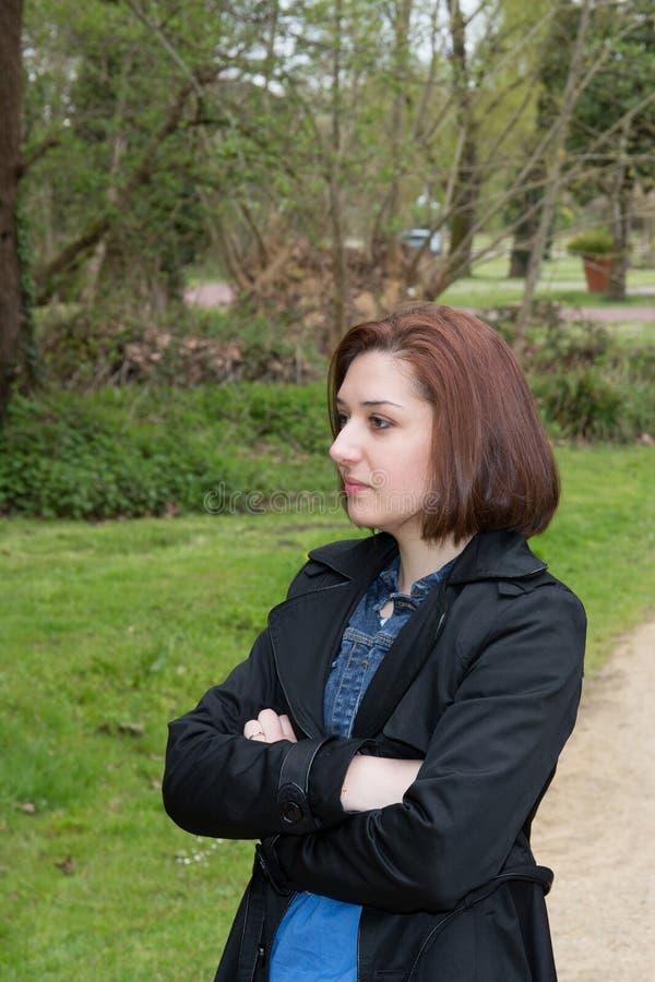 förhållandesvårigheter kämpar och familjbegreppet med korsade utomhus- armar för den olyckliga ilskna flickan royaltyfri bild