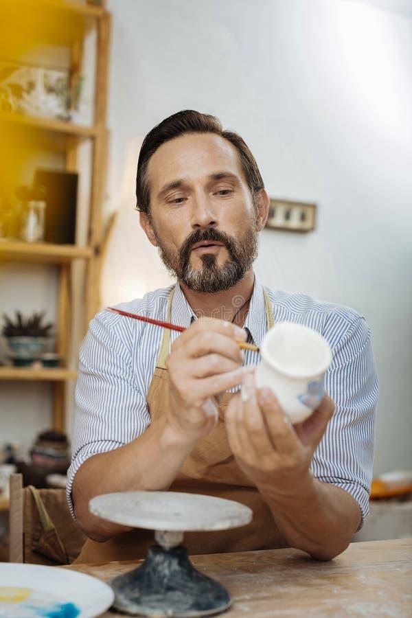 Förkläde och arbete för svartögd skäggig ceramist bärande arkivbild
