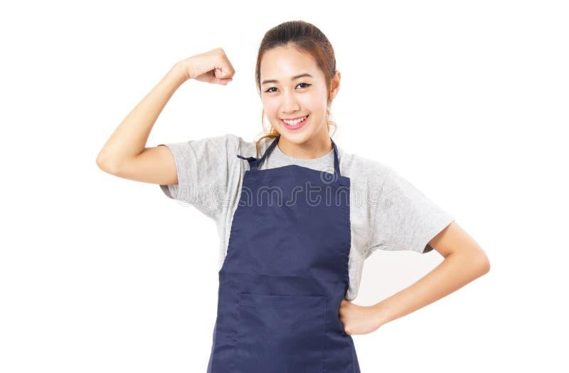 Förkläde och Flex Her Muscles för asiatisk kvinna bärande arkivfoton