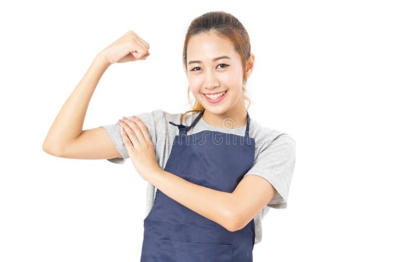 Förkläde och Flex Her Muscles för asiatisk kvinna bärande royaltyfri bild