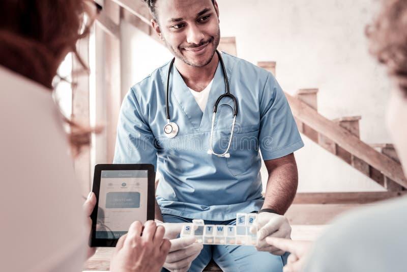 Förklarande patient för gladlynt doktor hans behandlingsmetod arkivbild