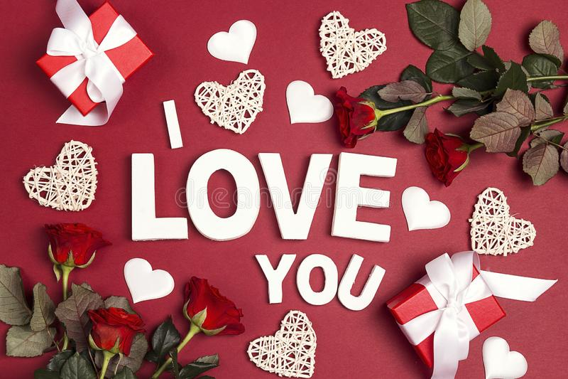 Förklaring av förälskelse med gåvor, rosa blommor och dekorativa hjärtor på röd bakgrund Begrepp för St-valentindag royaltyfri bild