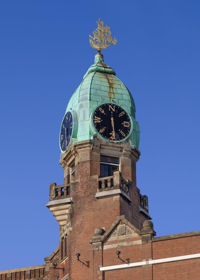 Förkoppra det dolda tornet med en klocka på en klassisk tegelstenbyggnad arkivfoto