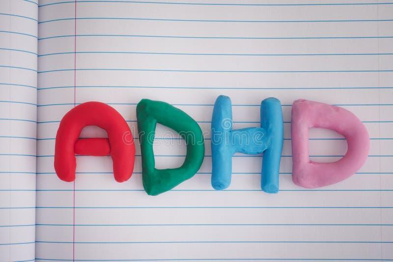Förkortning ADHD som göras ut ur plasticine på anteckningsbokarket arkivfoton