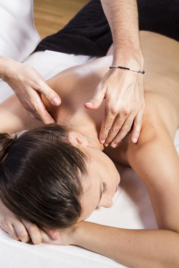 Förkroppsliga den härliga brunettkvinnan som får en massage arkivbild
