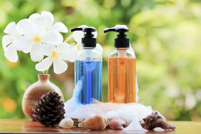 Förkroppsliga den omsorgprodukten, duschen, schampo, lotion och frangipanien eller plumer royaltyfria bilder