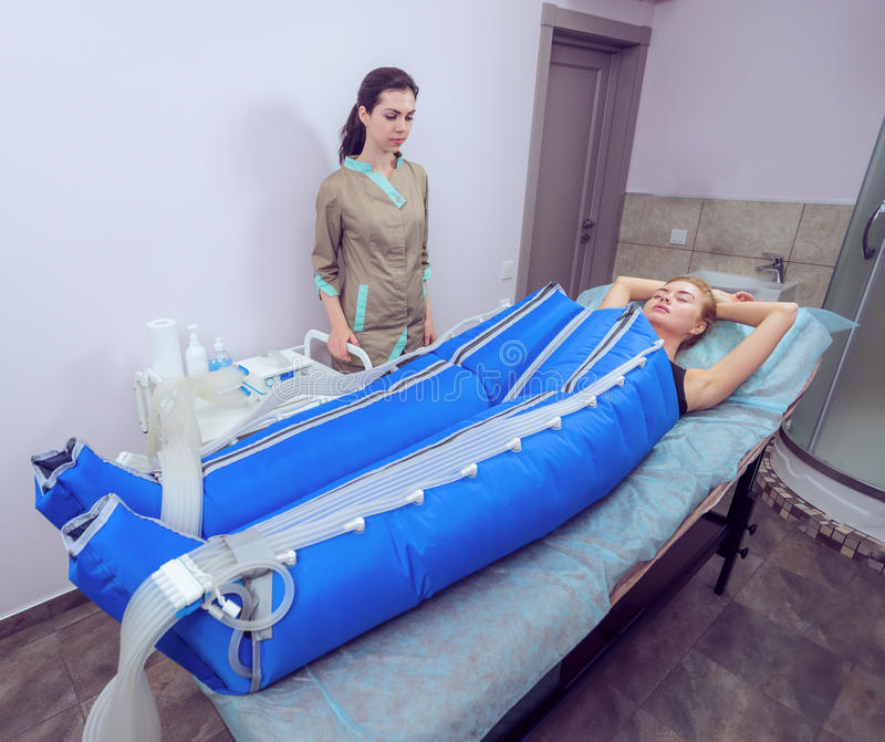 Förkroppsliga den pressotherapy maskinen på kvinna i skönhetmitt royaltyfria foton