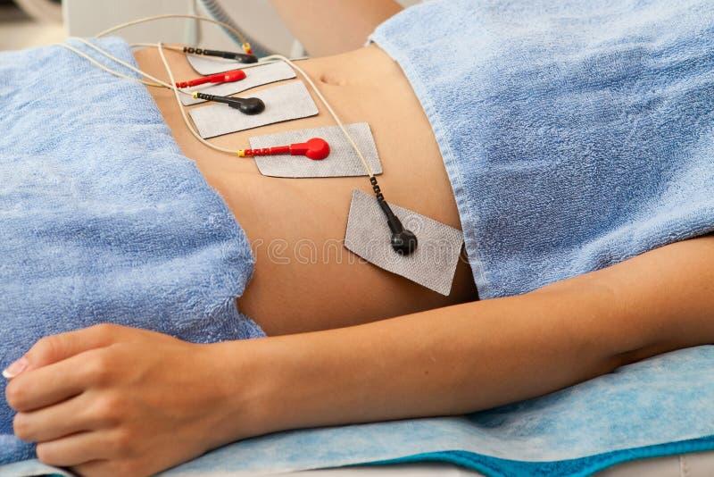 Förkroppsliga kosmetisk behandling med silkespapperelektronstimulans på ung kvinna royaltyfri foto