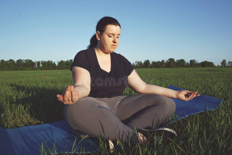 Förkroppsliga realiteten, yoga, meditationen, lugn, koppla av övervikt royaltyfri foto