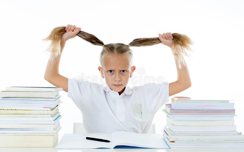Förkrossad liten flicka med en negativ inställning in mot studier och skola når att ha studerat för mycket och att ha haft för må royaltyfri fotografi