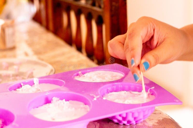 Förkylning häller rosa färgtvålblandningen som hälls in i rosa former för hemmet gjord tvål arkivbild