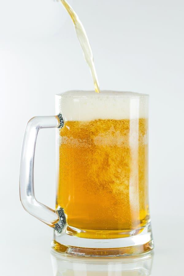 Förkylning rånar av öl med skum som isoleras på den snabba banan för vit bakgrund arkivbilder