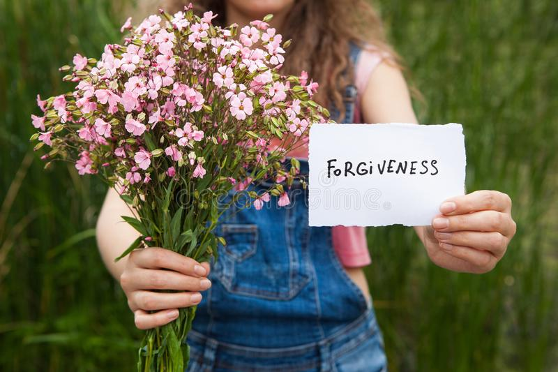 Förlåtelse - kvinna med ord och buketten av rosa blommor arkivbilder