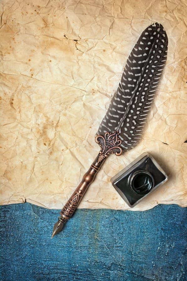 Förlöjliga upp av det tomma tappningpappersarket med fjäderpennan och flaskan av svart färgpulver royaltyfria foton